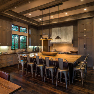 Example of a large mountain style l-shaped dark wood floor eat-in kitchen design in Sacramento with paneled appliances, an island, a farmhouse sink, shaker cabinets, dark wood cabinets, gray backsplash and subway tile backsplash