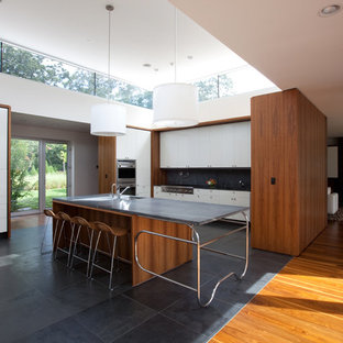 Design ideas for a modern u-shaped open plan kitchen in Other with soapstone benchtops, an undermount sink, flat-panel cabinets, white cabinets, black splashback, stainless steel appliances and slate floors.