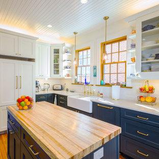 Klassisk inredning av ett avskilt l-kök, med en rustik diskho, skåp i shakerstil, blå skåp, vitt stänkskydd, stänkskydd i tunnelbanekakel, integrerade vitvaror, mellanmörkt trägolv, en köksö och orange golv
