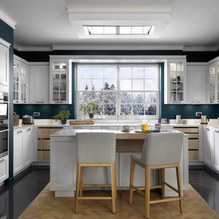 Inspiration for a traditional u-shaped kitchen in London with shaker cabinets, white cabinets, blue splashback, an island, black floors and white worktops.
