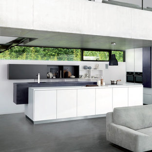 Modern u-shaped open plan kitchen in London with flat-panel cabinets, white cabinets, black appliances, an island, grey floors and white worktops.