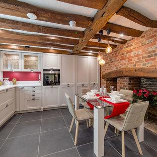 Immagine di una cucina contemporanea di medie dimensioni con lavello sottopiano, ante con riquadro incassato, paraspruzzi rosso, nessuna isola, pavimento nero, top bianco, ante grigie e elettrodomestici da incasso