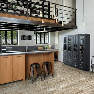 Foto på ett funkis grå parallellkök, med en undermonterad diskho, släta luckor, skåp i mellenmörkt trä, grått stänkskydd, tegelgolv, en halv köksö och brunt golv