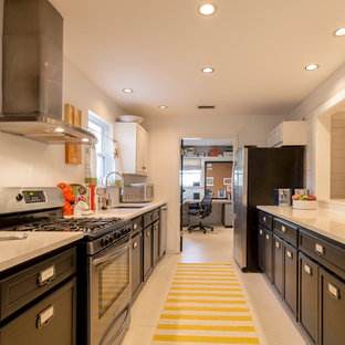 Photo of a small nautical kitchen in Miami with a submerged sink, recessed-panel cabinets, dark wood cabinets, composite countertops, white splashback, stainless steel appliances and plywood flooring.