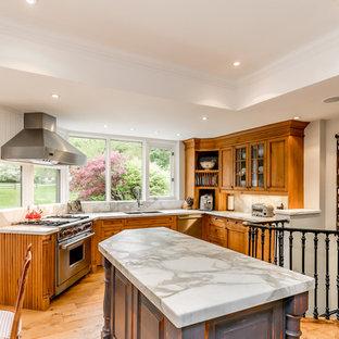 トロントの中くらいのカントリー風おしゃれなキッチン (アンダーカウンターシンク、落し込みパネル扉のキャビネット、中間色木目調キャビネット、大理石カウンター、白いキッチンパネル、大理石のキッチンパネル、シルバーの調理設備、淡色無垢フローリング、黄色い床、白いキッチンカウンター) の写真