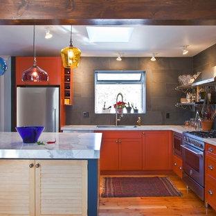 Idee per una cucina a L eclettica con elettrodomestici in acciaio inossidabile, ante arancioni, paraspruzzi grigio, paraspruzzi con piastrelle in pietra e ante con riquadro incassato