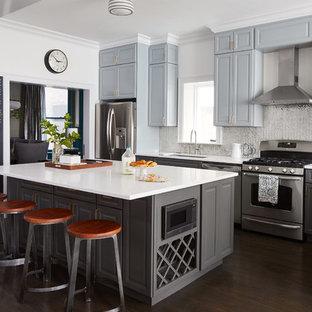 Inredning av ett klassiskt mellanstort kök, med en undermonterad diskho, luckor med upphöjd panel, grå skåp, stänkskydd med metallisk yta, rostfria vitvaror, mörkt trägolv, en köksö, brunt golv, bänkskiva i kvarts och spegel som stänkskydd