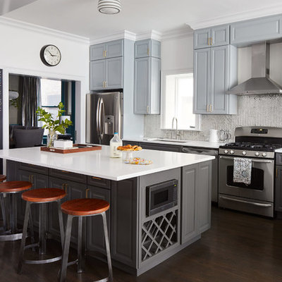 Inspiration for a mid-sized transitional l-shaped dark wood floor and brown floor open concept kitchen remodel in Chicago with an undermount sink, raised-panel cabinets, gray cabinets, metallic backsplash, stainless steel appliances, an island, quartz countertops and mirror backsplash