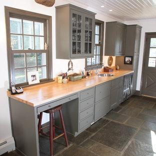 フィラデルフィアのカントリー風おしゃれなキッチン (フラットパネル扉のキャビネット、木材カウンター、グレーのキャビネット、スレートの床) の写真