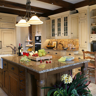 This is an example of a large traditional u-shaped eat-in kitchen in New York with a farmhouse sink, beaded inset cabinets, yellow cabinets, granite benchtops, multi-coloured splashback, slate splashback, panelled appliances, limestone floors, with island, yellow floor and brown benchtop.