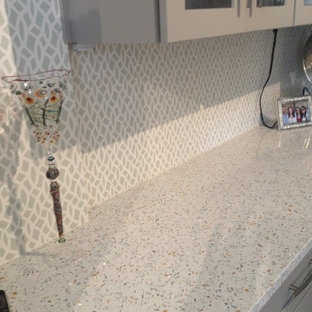 Inspiration for an expansive transitional u-shaped kitchen pantry in Charlotte with no island, raised-panel cabinets, beige cabinets, recycled glass benchtops, grey splashback, glass tile splashback, stainless steel appliances, a farmhouse sink and porcelain floors.