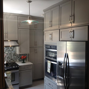 This is an example of a small transitional u-shaped kitchen pantry in Charlotte with no island, raised-panel cabinets, beige cabinets, recycled glass benchtops, grey splashback, glass tile splashback, stainless steel appliances, a farmhouse sink and porcelain floors.
