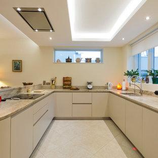 Ispirazione per una cucina minimal di medie dimensioni con lavello sottopiano, ante lisce, ante beige, top in granito e nessuna isola