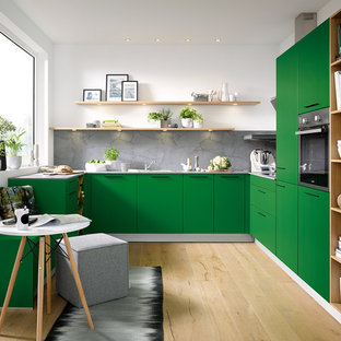 Contemporary kitchen designs - Trendy u-shaped light wood floor and beige floor kitchen photo in Other with flat-panel cabinets, green cabinets, gray backsplash and paneled appliances