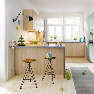 Photo of a contemporary u-shaped kitchen in Other with flat-panel cabinets, green cabinets, white splashback, integrated appliances, light hardwood flooring, a breakfast bar and beige floors.