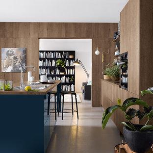Пример оригинального дизайна интерьера: параллельная кухня в современном стиле с накладной раковиной, плоскими фасадами, фасадами цвета дерева среднего тона, столешницей из дерева, островом и белым полом
