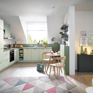 This is an example of a contemporary l-shaped open plan kitchen in Other with flat-panel cabinets, green cabinets, integrated appliances, light hardwood flooring and brown floors.