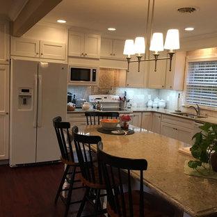 他の地域の大きいトラディショナルスタイルのおしゃれなキッチン (アンダーカウンターシンク、シェーカースタイル扉のキャビネット、白いキャビネット、クオーツストーンカウンター、ベージュキッチンパネル、ライムストーンの床、白い調理設備、濃色無垢フローリング、赤い床、ベージュのキッチンカウンター) の写真
