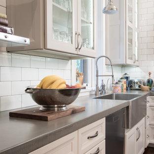 セントルイスの中サイズのインダストリアルスタイルのおしゃれなキッチン (エプロンフロントシンク、シェーカースタイル扉のキャビネット、白いキャビネット、ステンレスカウンター、白いキッチンパネル、サブウェイタイルのキッチンパネル、シルバーの調理設備の、濃色無垢フローリング、茶色い床) の写真