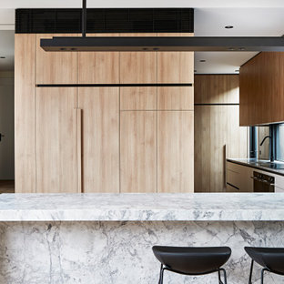 Contemporary u-shaped kitchen in Melbourne with flat-panel cabinets, medium wood cabinets, black splashback, panelled appliances, medium hardwood floors, a peninsula, brown floor and multi-coloured benchtop.