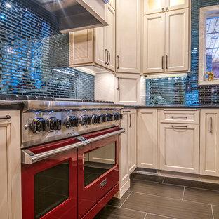 フィラデルフィアの大きいエクレクティックスタイルのおしゃれなキッチン (エプロンフロントシンク、落し込みパネル扉のキャビネット、白いキャビネット、御影石カウンター、青いキッチンパネル、ガラスタイルのキッチンパネル、カラー調理設備、磁器タイルの床、黒い床、黒いキッチンカウンター) の写真