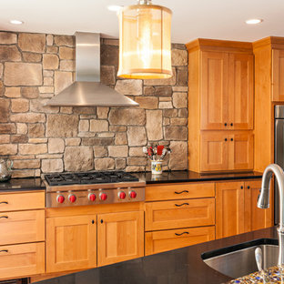 Inspiration for a mid-sized transitional u-shaped eat-in kitchen in Boston with shaker cabinets, medium wood cabinets, recycled glass benchtops, brown splashback, with island, an undermount sink, stone tile splashback and stainless steel appliances.