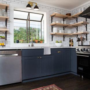 ラスベガスの小さいエクレクティックスタイルのおしゃれなキッチン (アンダーカウンターシンク、シェーカースタイル扉のキャビネット、グレーのキャビネット、珪岩カウンター、白いキッチンパネル、サブウェイタイルのキッチンパネル、シルバーの調理設備の、濃色無垢フローリング、茶色い床) の写真