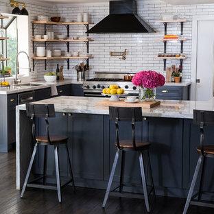 ラスベガスの小さいエクレクティックスタイルのおしゃれなキッチン (アンダーカウンターシンク、シェーカースタイル扉のキャビネット、グレーのキャビネット、珪岩カウンター、白いキッチンパネル、サブウェイタイルのキッチンパネル、シルバーの調理設備、濃色無垢フローリング、茶色い床) の写真
