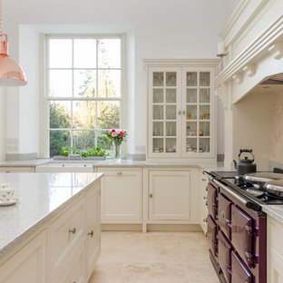Inspiration for a large traditional l-shaped kitchen/diner in London with a belfast sink, shaker cabinets, white cabinets, granite worktops, beige splashback, limestone splashback, coloured appliances, limestone flooring, an island, beige floors and grey worktops.