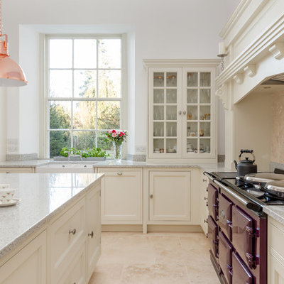 Eat-in kitchen - large traditional l-shaped limestone floor and beige floor eat-in kitchen idea in London with a farmhouse sink, shaker cabinets, white cabinets, granite countertops, beige backsplash, limestone backsplash, colored appliances, an island and gray countertops