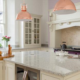 Große Klassische Wohnküche in L-Form mit Landhausspüle, Schrankfronten im Shaker-Stil, weißen Schränken, Granit-Arbeitsplatte, Küchenrückwand in Beige, Kalk-Rückwand, bunten Elektrogeräten, Kalkstein, Kücheninsel, beigem Boden und grauer Arbeitsplatte in London