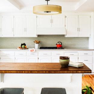 Esempio di una grande cucina chic con ante con bugna sagomata, ante bianche, top in quarzo composito, paraspruzzi verde, paraspruzzi con piastrelle di vetro, pavimento in legno massello medio e isola