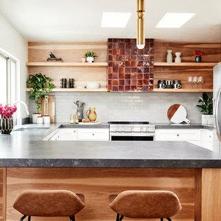 サクラメントのサンタフェスタイルのおしゃれなキッチン (シングルシンク、シェーカースタイル扉のキャビネット、白いキャビネット、白いキッチンパネル、サブウェイタイルのキッチンパネル、シルバーの調理設備、グレーのキッチンカウンター) の写真