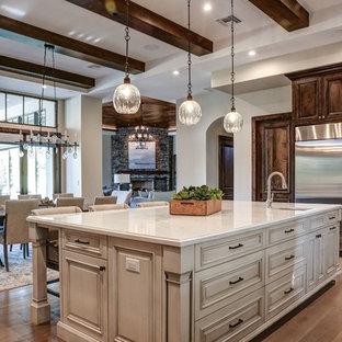 フェニックスの広いコンテンポラリースタイルのおしゃれなキッチン (ドロップインシンク、レイズドパネル扉のキャビネット、濃色木目調キャビネット、クオーツストーンカウンター、白いキッチンパネル、セラミックタイルのキッチンパネル、シルバーの調理設備、淡色無垢フローリング、茶色い床、白いキッチンカウンター) の写真