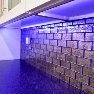 Bild på ett mellanstort funkis flerfärgad flerfärgat kök, med en undermonterad diskho, skåp i shakerstil, vita skåp, granitbänkskiva, stänkskydd med metallisk yta, glaspanel som stänkskydd, rostfria vitvaror, klinkergolv i porslin, en köksö och beiget golv