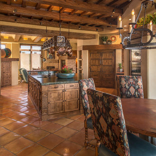 Large southwestern kitchen appliance - Large southwest terra-cotta floor kitchen photo in Phoenix with flat-panel cabinets, distressed cabinets, solid surface countertops and an island