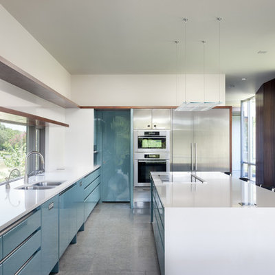 Example of a 1950s kitchen design in Austin with stainless steel appliances, quartz countertops, a double-bowl sink and flat-panel cabinets