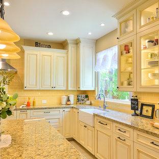 サンディエゴの巨大なトラディショナルスタイルのおしゃれなキッチン (エプロンフロントシンク、レイズドパネル扉のキャビネット、ベージュのキャビネット、御影石カウンター、黄色いキッチンパネル、セラミックタイルのキッチンパネル、シルバーの調理設備の、磁器タイルの床) の写真