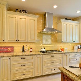 Immagine di un'ampia cucina classica con lavello stile country, ante con bugna sagomata, ante beige, top in granito, paraspruzzi giallo, paraspruzzi con piastrelle in ceramica, elettrodomestici in acciaio inossidabile, pavimento in gres porcellanato e isola