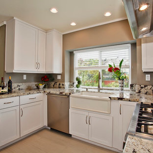 Cottage u-shaped eat-in kitchen photo in San Diego with a farmhouse sink, flat-panel cabinets, white cabinets, granite countertops, gray backsplash, stone slab backsplash and stainless steel appliances