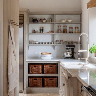 グロスタシャーの広いカントリー風おしゃれなキッチン (シングルシンク、レイズドパネル扉のキャビネット、大理石カウンター、白いキッチンパネル、石スラブのキッチンパネル、シルバーの調理設備、ライムストーンの床、ベージュのキャビネット) の写真