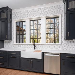 Idéer för att renovera ett mellanstort vintage vit vitt kök, med en rustik diskho, blå skåp, marmorbänkskiva, vitt stänkskydd, stänkskydd i mosaik, rostfria vitvaror, mellanmörkt trägolv och brunt golv