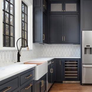 Diseño de cocina en L, clásica, de tamaño medio, con despensa, fregadero sobremueble, puertas de armario azules, encimera de mármol, salpicadero blanco, salpicadero con mosaicos de azulejos, electrodomésticos de acero inoxidable, suelo de madera en tonos medios, suelo marrón y encimeras blancas