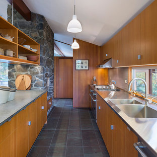 Photo of a large midcentury galley eat-in kitchen in Boston with a double-bowl sink, medium wood cabinets, stainless steel benchtops, grey splashback, stone tile splashback, stainless steel appliances, slate floors, flat-panel cabinets and no island.