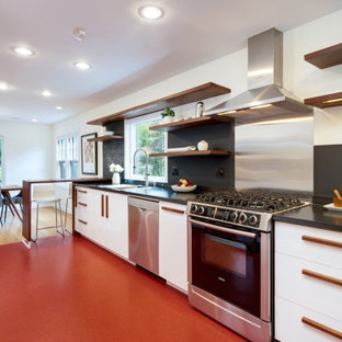 This is an example of a midcentury eat-in kitchen in Portland with flat-panel cabinets, white cabinets, black splashback, stainless steel appliances, a peninsula, red floor and black benchtop.
