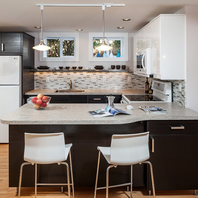 Inspiration for a mid-sized contemporary u-shaped light wood floor and beige floor eat-in kitchen remodel in Portland with a single-bowl sink, flat-panel cabinets, dark wood cabinets, solid surface countertops, multicolored backsplash, glass tile backsplash, white appliances and a peninsula