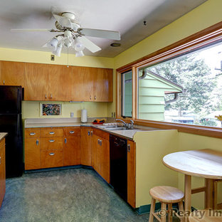 Inspiration for a mid-sized midcentury u-shaped eat-in kitchen in Portland with a drop-in sink, flat-panel cabinets, medium wood cabinets, laminate benchtops, beige splashback, black appliances and linoleum floors.