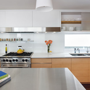 Minimalist kitchen photo in San Francisco with stainless steel appliances, a double-bowl sink, flat-panel cabinets, light wood cabinets, white backsplash, glass sheet backsplash and solid surface countertops