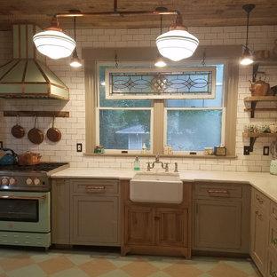 ニューヨークの小さいエクレクティックスタイルのおしゃれなキッチン (エプロンフロントシンク、落し込みパネル扉のキャビネット、グレーのキャビネット、人工大理石カウンター、白いキッチンパネル、モザイクタイルのキッチンパネル、カラー調理設備、塗装フローリング、アイランドなし、マルチカラーの床) の写真