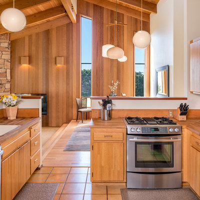Example of a small beach style galley ceramic tile enclosed kitchen design in San Francisco with a drop-in sink, flat-panel cabinets, medium tone wood cabinets, wood countertops, stainless steel appliances and a peninsula